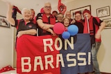 A group of people hold up a sign saying 'Ron Barassi' wearing Demons colours of red and blue.