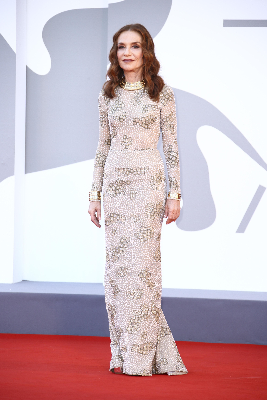 Isabelle Huppert indossa un abito a maniche lunghe bianco sporco con centinaia di piccoli abbellimenti scintillanti.
