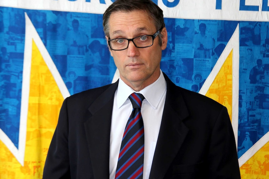 A mid shot of Mark olsen dressed in a suit and tie.