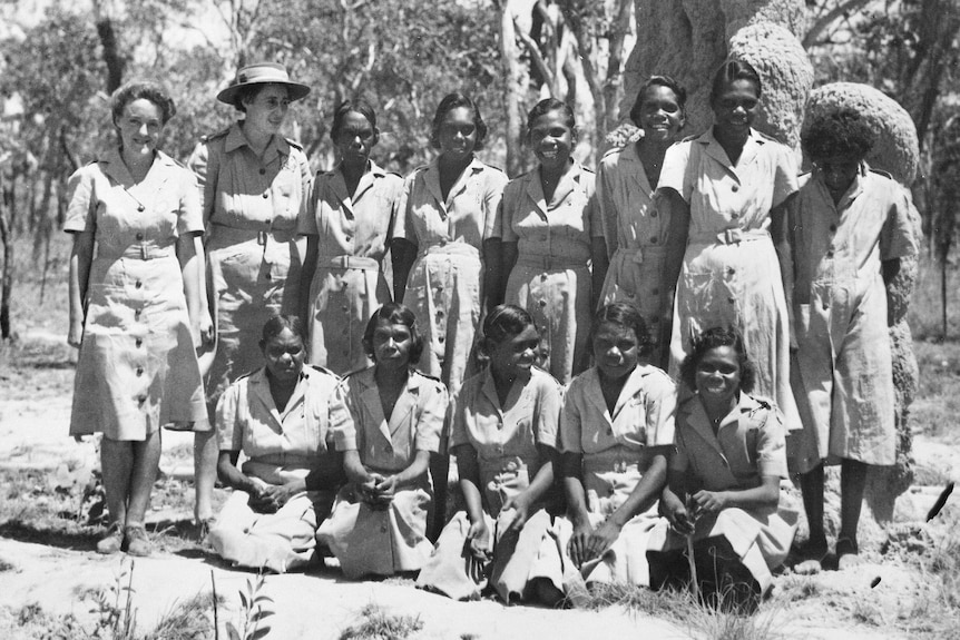 Corporal Dolly Garinyi Batcho sits in the front row of a group photo, with other women standing behind.