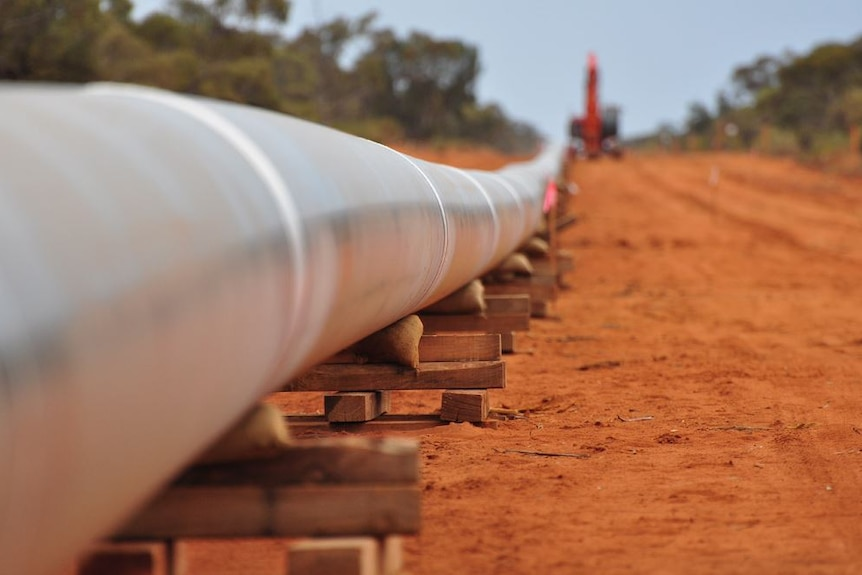 A section of metal pipeline stretching into the distance lies in wooden blocks on the ground, with a crane in the background.