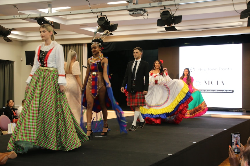 Models from diverse backgrounds and dressed in unique outfits walk along a catwalk at a fashion show.