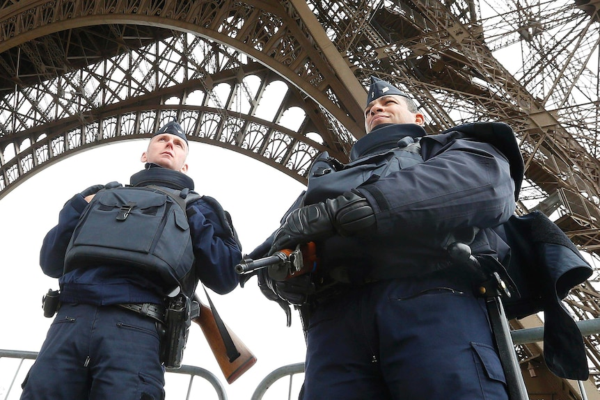 Police take up position under the Eiffel Tower the morning after a series of deadly attacks in Paris, on November 14, 2015.