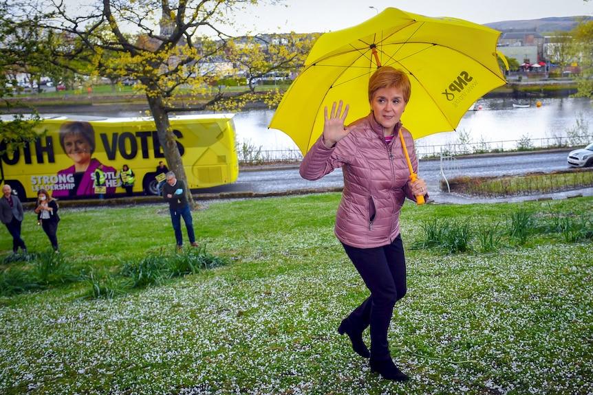 Nicola Sturgeon waves while holding a bright yellow umbrella