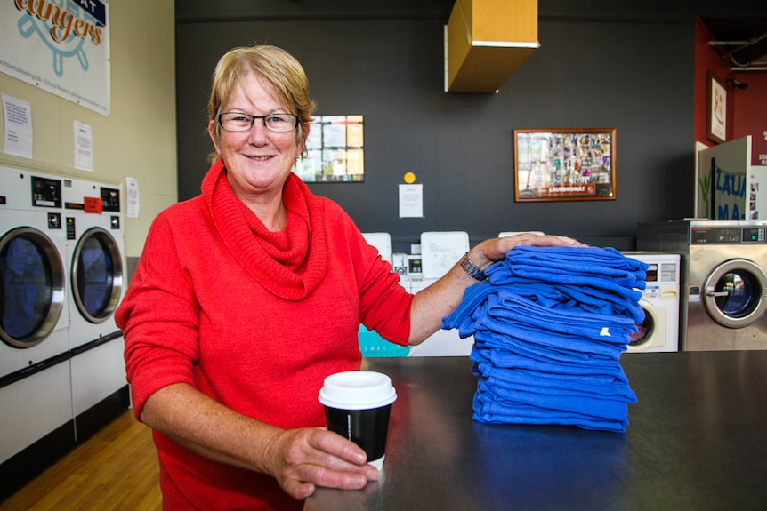 Coordinating Supervisor of Laundry Mates, Dianne Smith with a pile of blue towels.