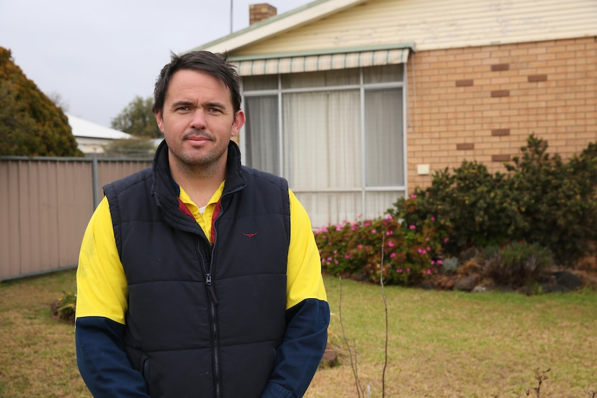 A man stands in front of a brick rental property.