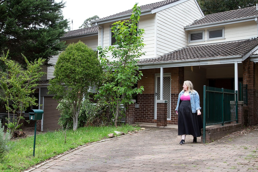 A woman wearing pink and black looks at the exterior of a unit