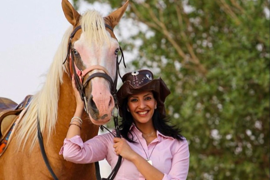A woman in a pink shirt and cowboy hat smiling next to a horse