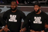 """Lakers players, including LeBron James and Anthony Davis, take a knee while arm in arm, wearing a """"BLACK LIVES MATTER"""" shirt"""