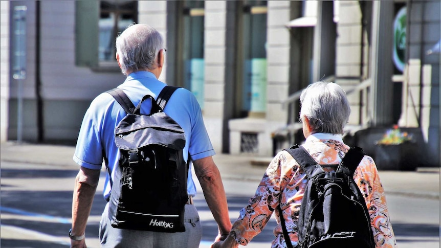 An older couple with grey hair and backpacks hold hands