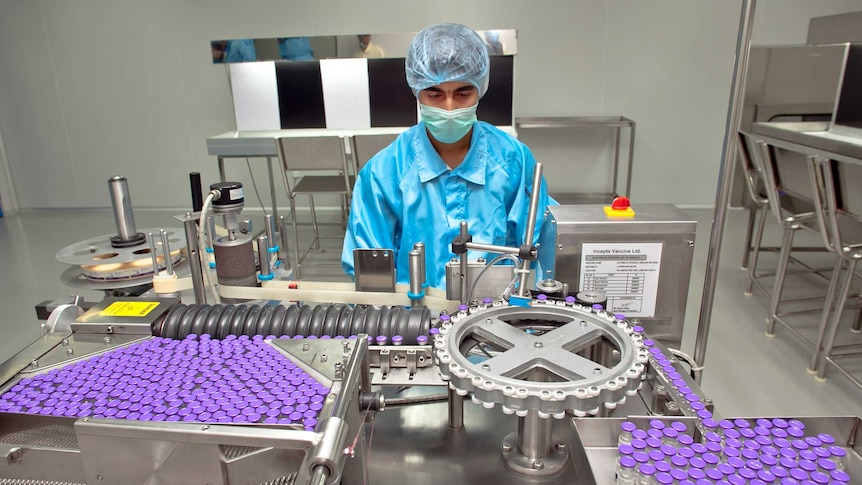 A man in PPE and a face mask examines a machine putting labels on purple medicine vials