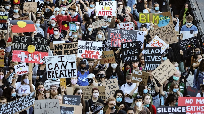 Crowd of people with masks holding Black Lives Matter signs in story about how to support BLM after it stops 'trending'.