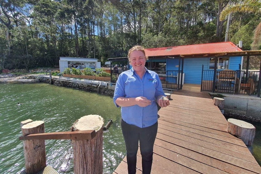 A woman stands on a jetty with an oyster in her hand.