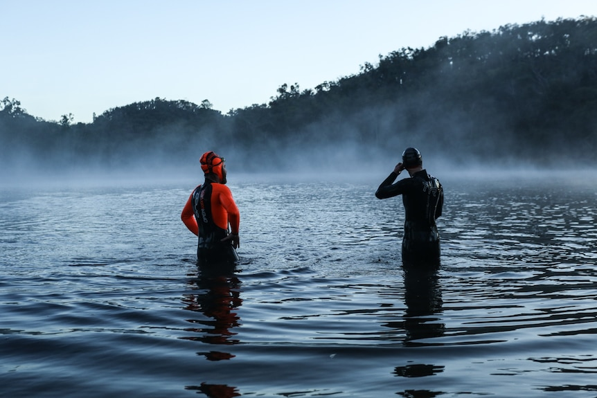 Jessie and Frog in their full length wetsuits standing in the water with their backs to the camera.