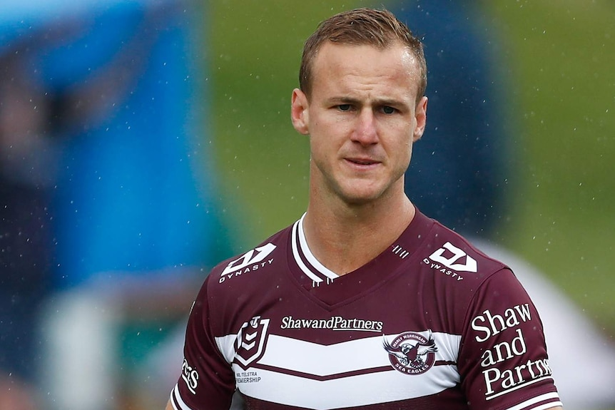 A Manly NRL player stands while holding a rugby league in his right hand.