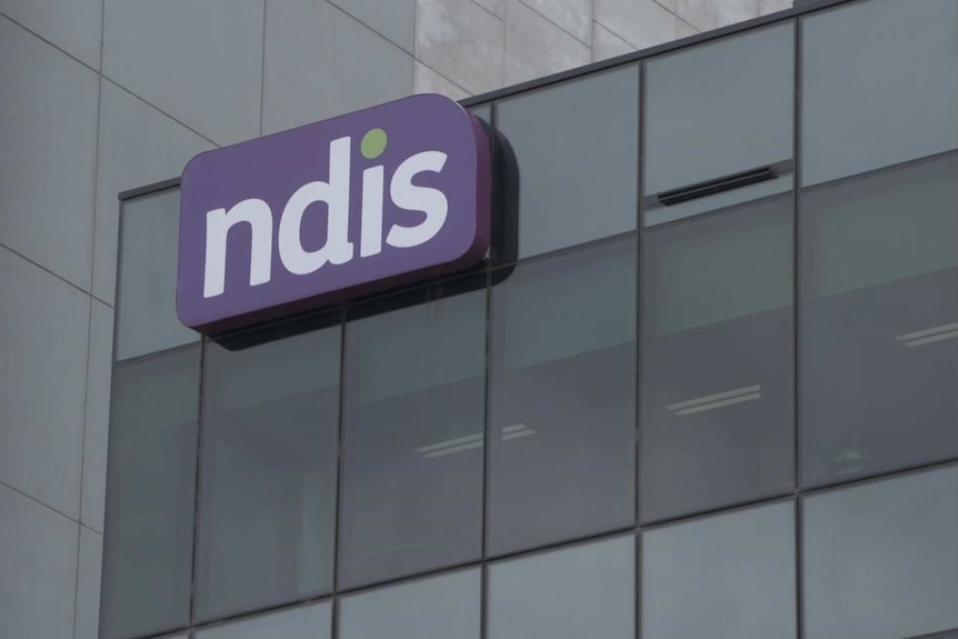 A purple NDIS sign on the side of an office building.