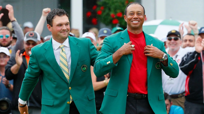 Patrick Reed places the green jacket on Tiger Woods at the 2019 Masters tournament.