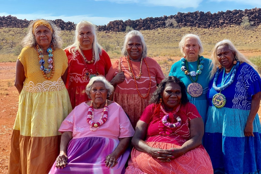 Community elders in colourful dresses pose for photo in front of desert with spinifex, wall of stacked large stones and blue sky