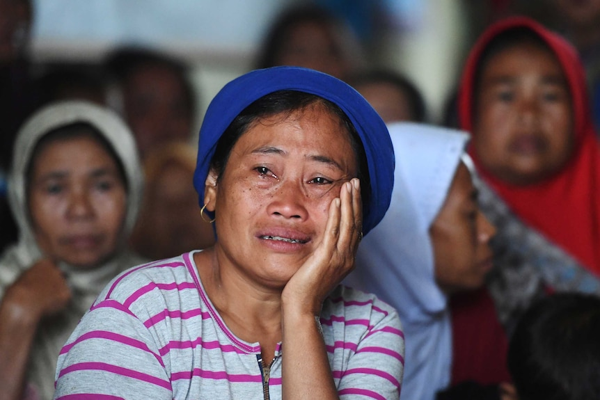 A young woman, wearing a blue hat and braces, holds her face as she cries with other women behind.