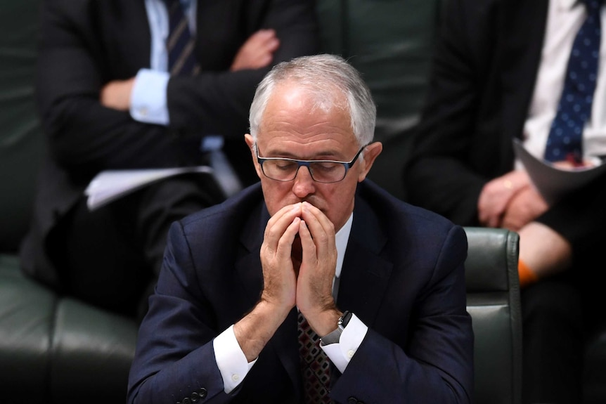 Malcolm Turnbull sits with his hands together in front of his face, eyes closed.