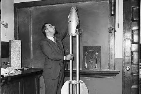 A black and white image of a man in a suit reaching up to the top of a rocket shaped time capsule