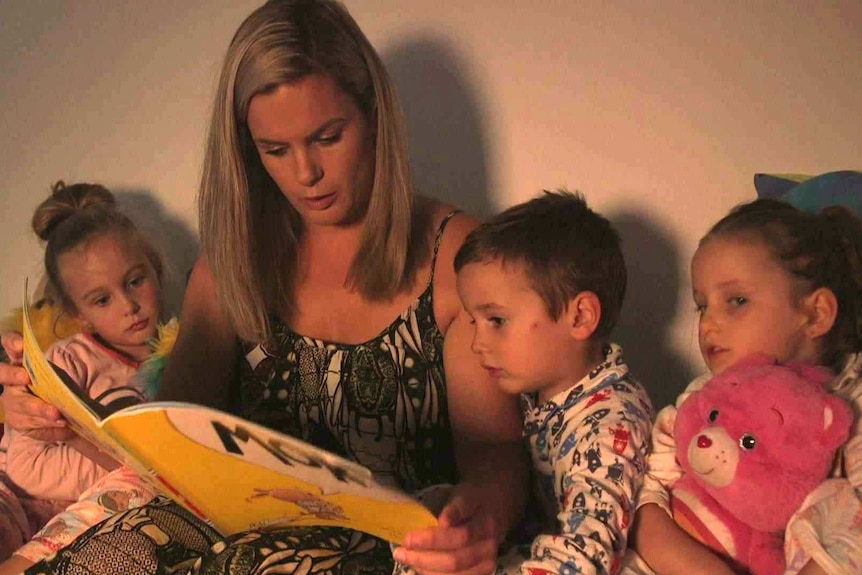 Corinne Merrigan reads from a picture book as her children listen.