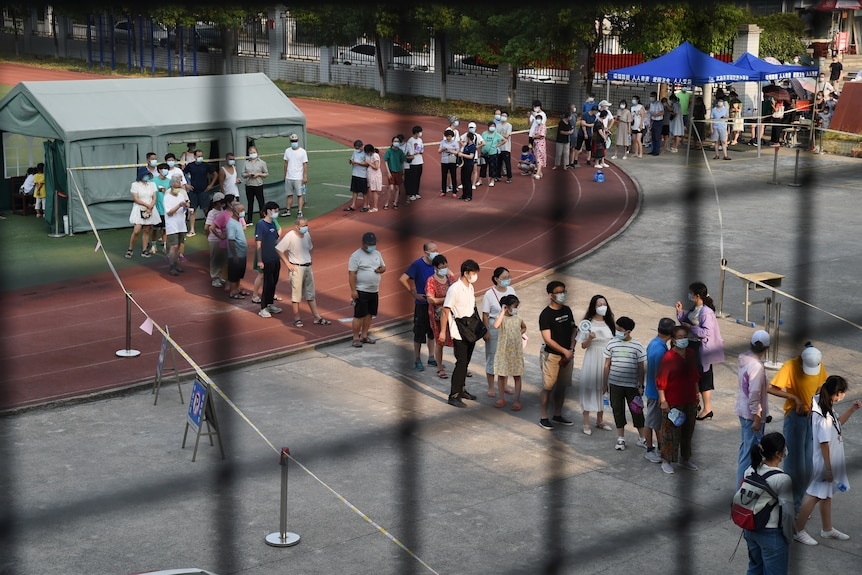 Residents stand in a long queue at a nucleic testing site in Wuhan