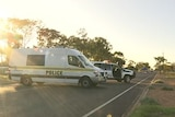 A police van and four-wheel-drive parked on a road