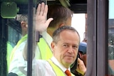 Bill Shorten waves to the media from inside the glass cab of large forklift.