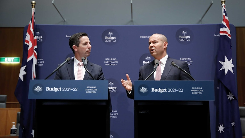 Two men in suits stand in front of podiums and banners marketing the 2021 budget, with Australian flags standing on either side.