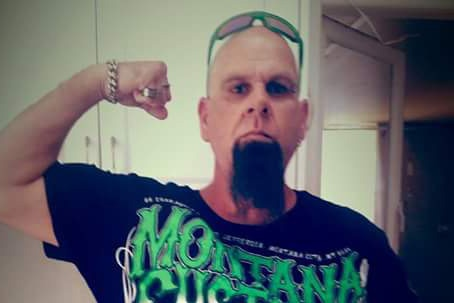 A man with a long goatee and sunglasses on his bald head stands posing for a photo pulling a strong arm sign.