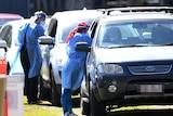 Health workers swab members of the public in their cars