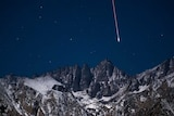 A meteor falls from the sky over a dramatic mountain range.