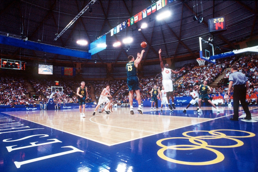 wide and low photo of a basketball court at the 2000 olympics with a crowd present
