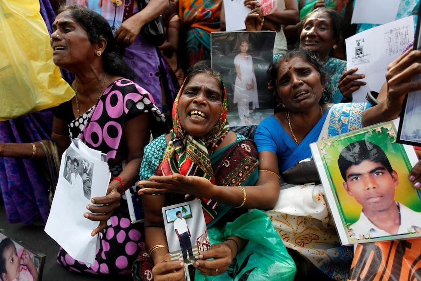 Women hold photos of young men allegedly disappeared in Sri Lanka