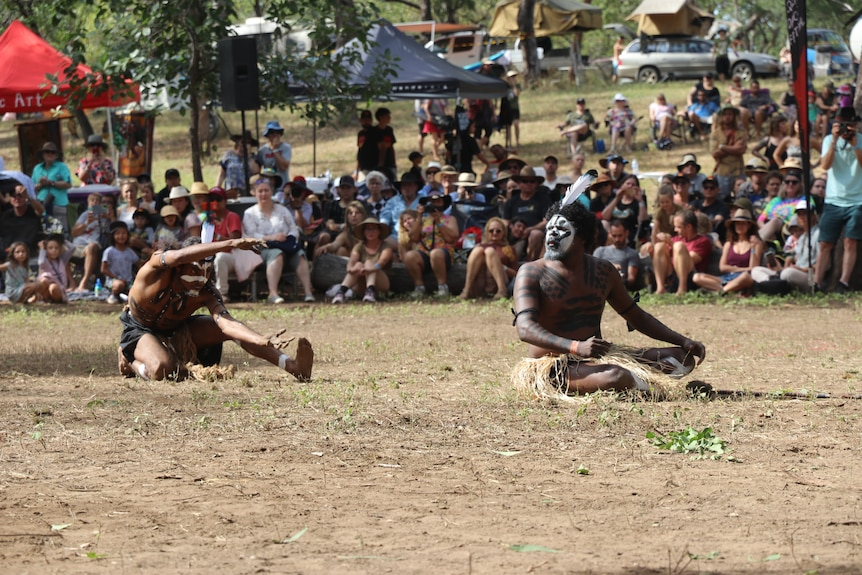 AN Aboriginal man moves his hands like a crocodile in a dance performance, locking his gaze on another dancer.