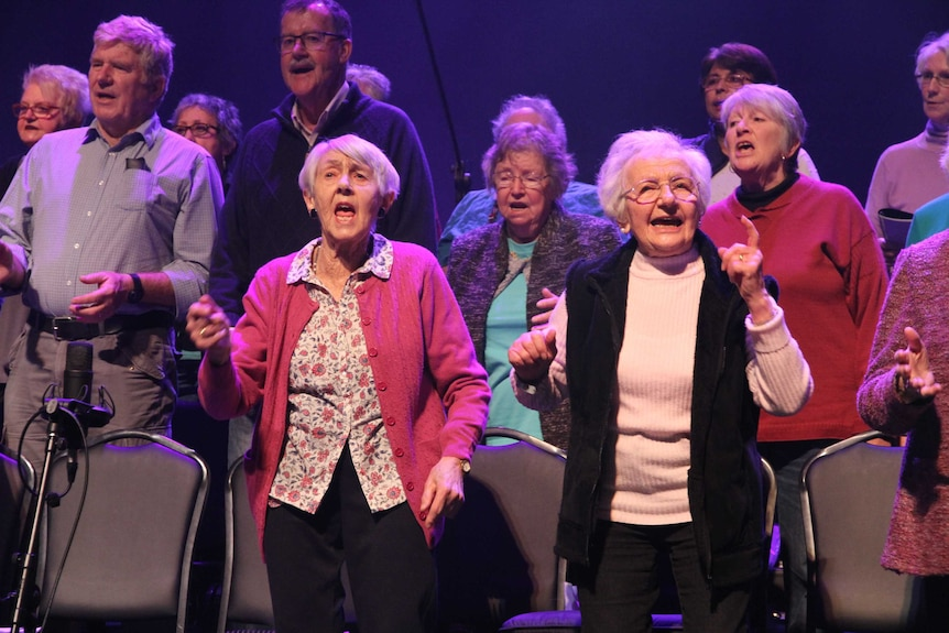 Two senior women sing in front of a choir. They are gesturing with their hands in time with the music.