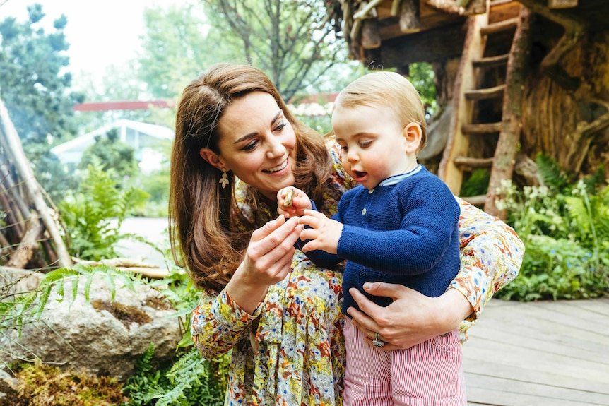 The Duchess of Cambridge looks at her son Prince Louis as he holds a flower