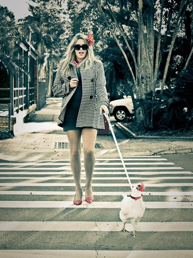 A blonde woman in a stylish outfit follows a chicken on a leash over a pedestrian crossing.