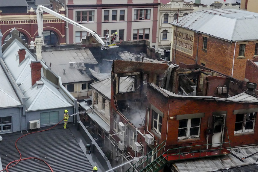 A roof of a city building is badly damaged by fire. You can see the interior of the top floor through tangled metal