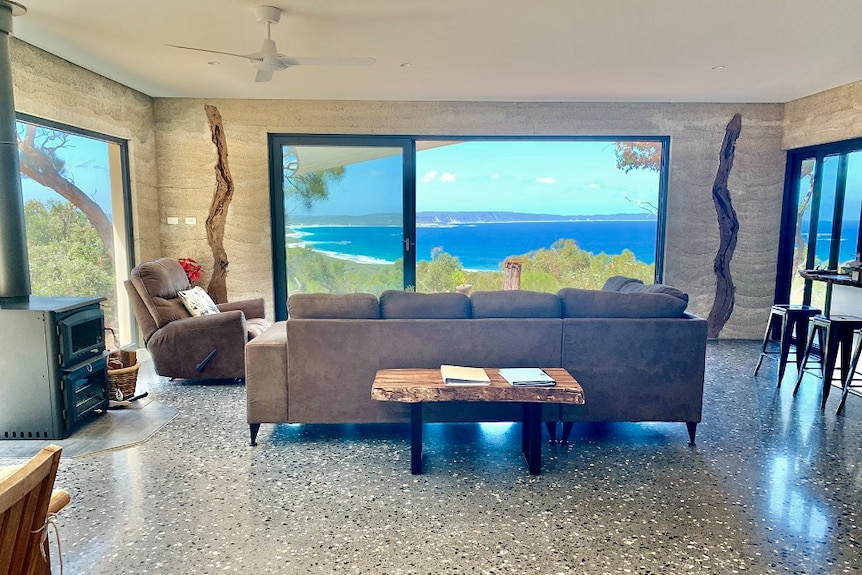 Looking through the living room in a house made of hemp towards the ocean on the southern coast of WA