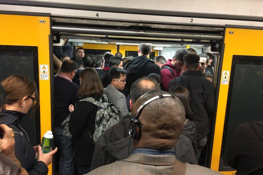 People crowd into a train carriage.