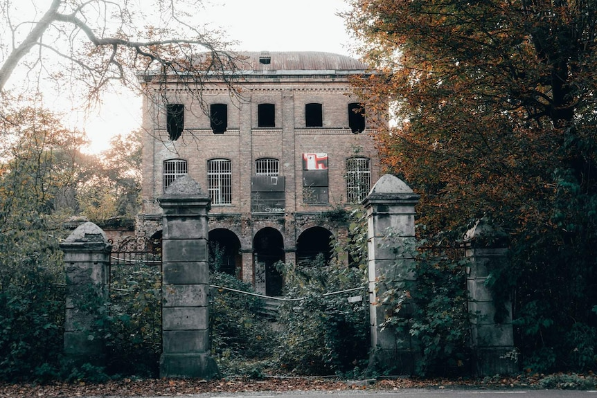 An old, dilapidated brick building in Germany with a fallen down fence and overgrown vegetation