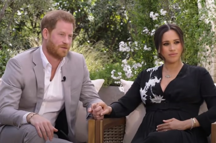 Prince Harry and Meghan Markle sitting on chairs and holding hands.