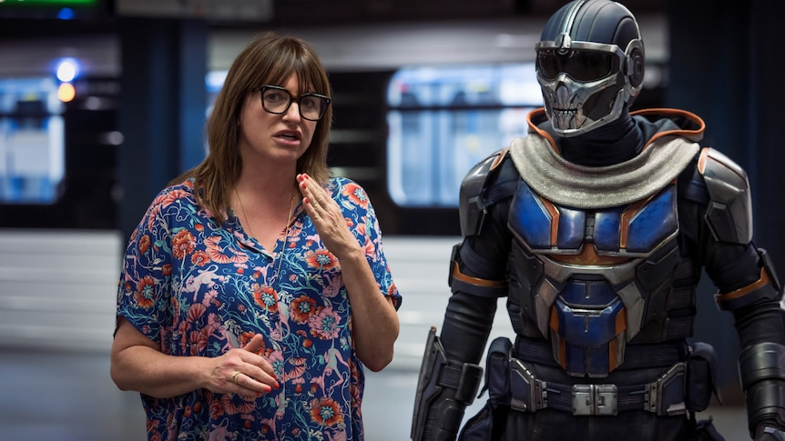 A woman in her early 50s in floral top with glasses directs someone in soldier/robot outfit