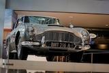 A silver car is seen on a raised platform behind a bollard.
