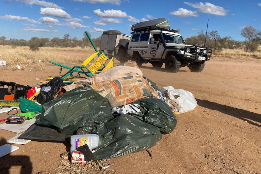 a pile of plastic rubbish bags next a dirt road