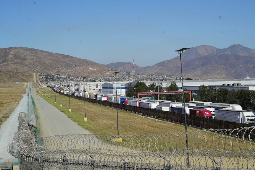 The US-Mexico border marked by a high, razor-wire fence.