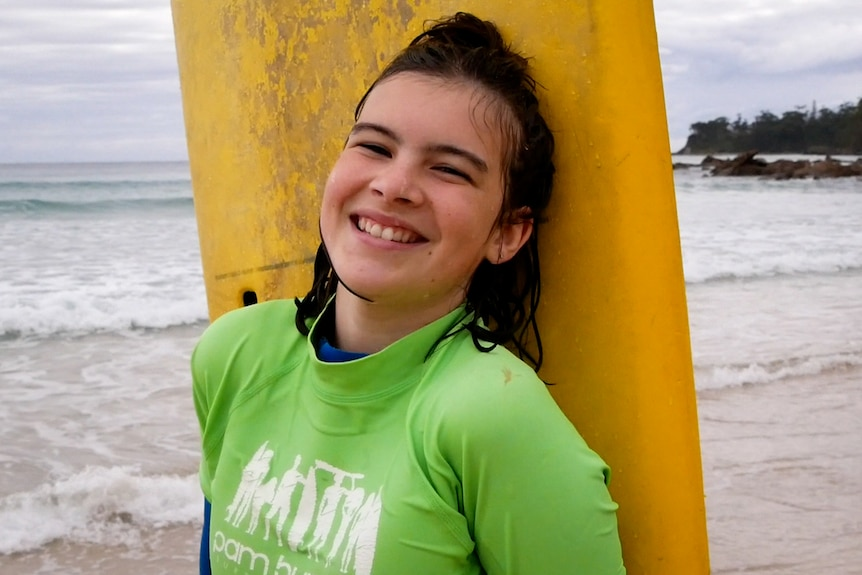 Young girl standing at the edge of beach with surfboard and huge smile