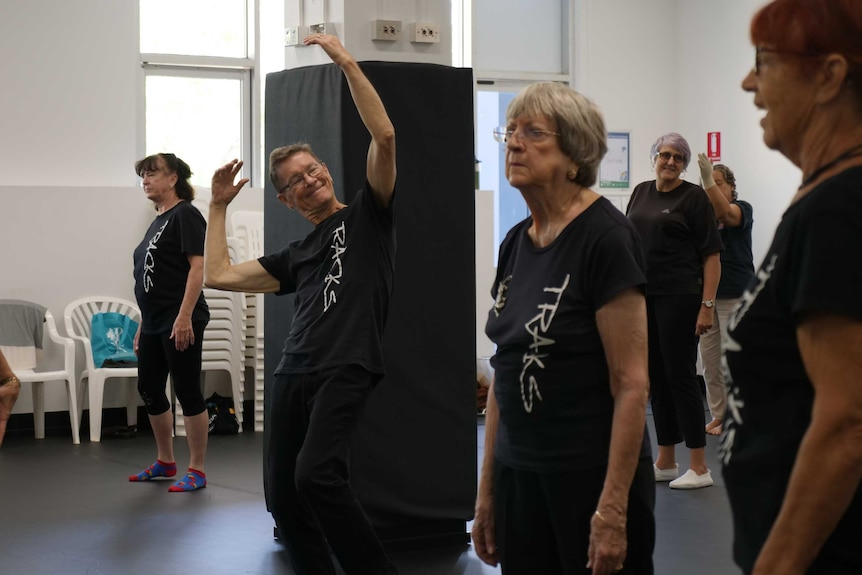 Dance studio rehearsal, Mr Butler standing in the centre with arms stretched above his head.
